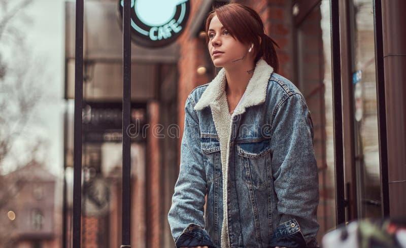 Menina do ruivo que veste a roupa na moda com os fones de ouvido sem fio que guardam o café afastado fora do café foto de stock royalty free