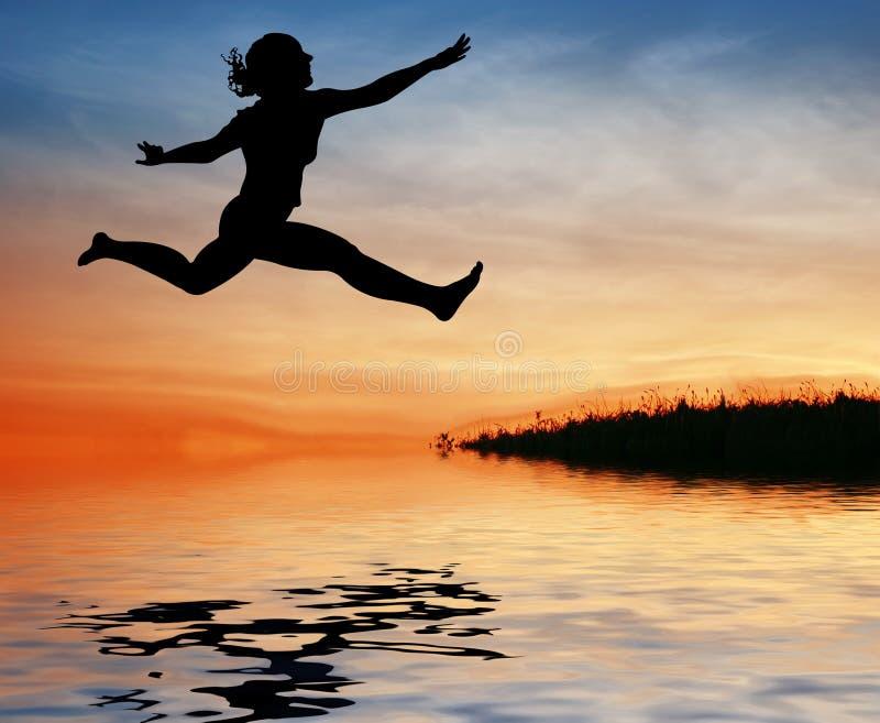 Menina do salto da silhueta na água foto de stock