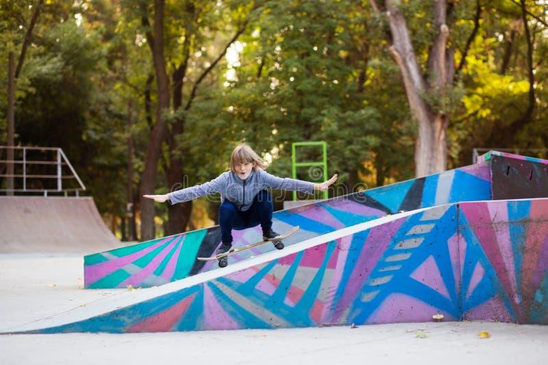 Menina do skater no skatepark que move sobre o skate fora foto de stock royalty free