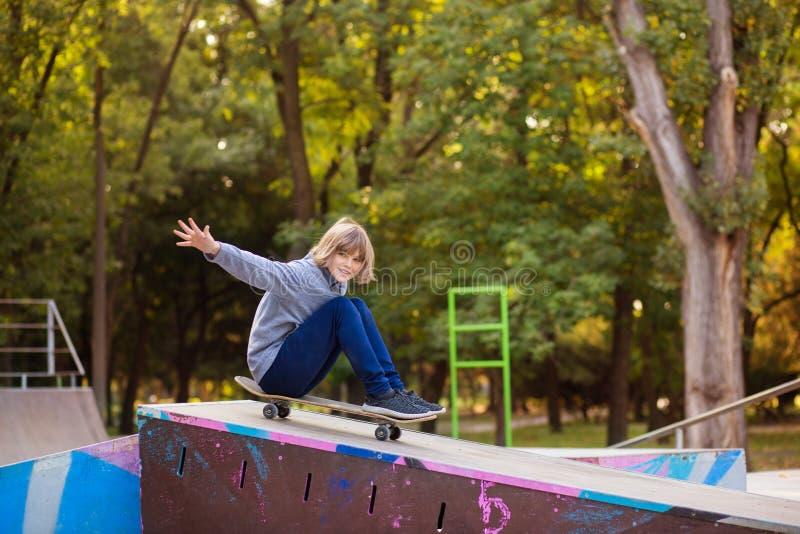 Menina do skater no skatepark que move sobre o skate fora fotografia de stock royalty free