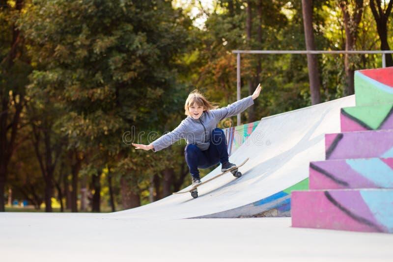 Menina do skater no skatepark que move sobre o skate fora fotos de stock