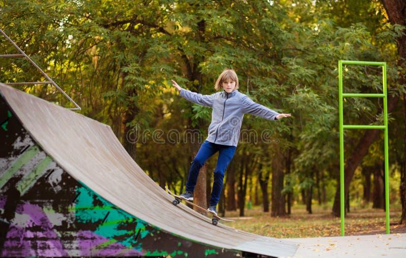 Menina do skater no skatepark que move sobre o skate fora fotos de stock royalty free