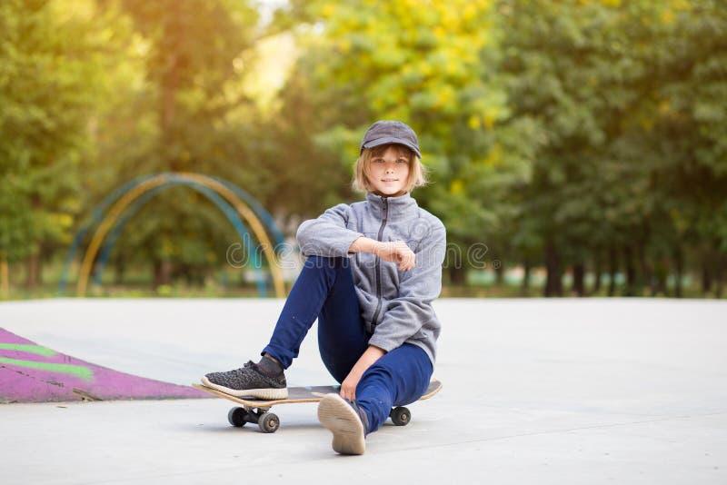 Menina do skater no skatepark que move sobre o skate fora imagem de stock
