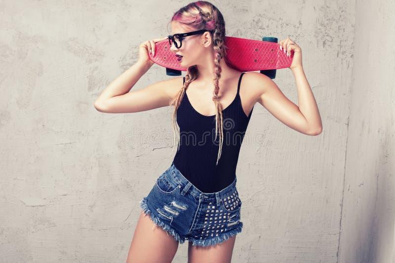 Menina do skater que levanta no estúdio imagens de stock royalty free