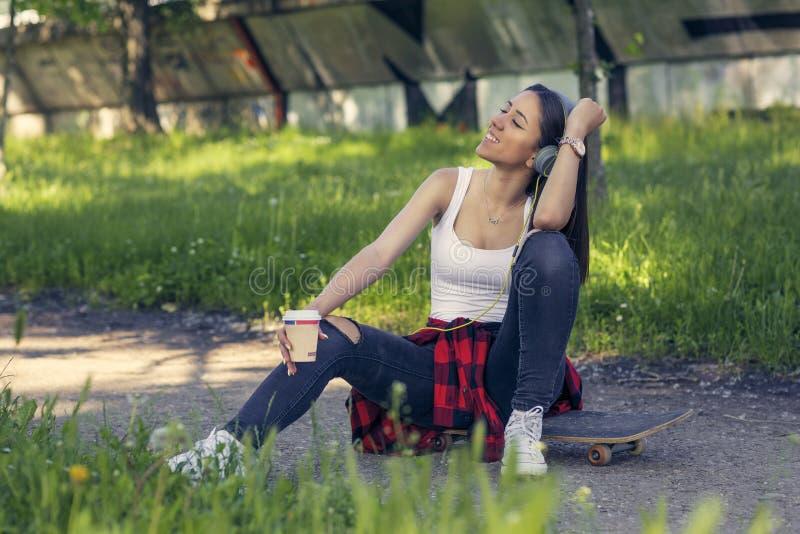 Menina do skater que senta-se no caf? da bebida do skate e na m?sica de escuta imagens de stock royalty free