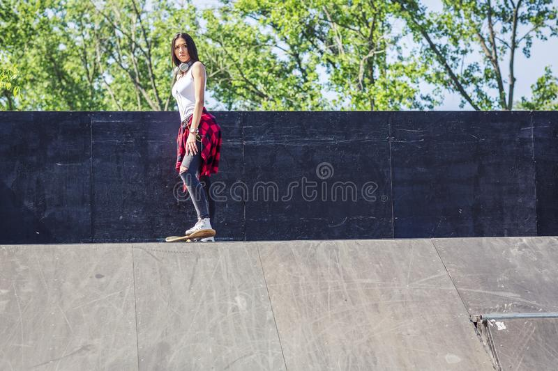 Menina do skater que skateboarding no parque do patim foto de stock royalty free