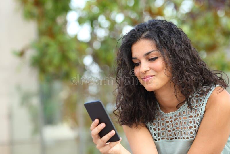 Menina do smiley que olha o índice esperto do telefone no parque foto de stock royalty free
