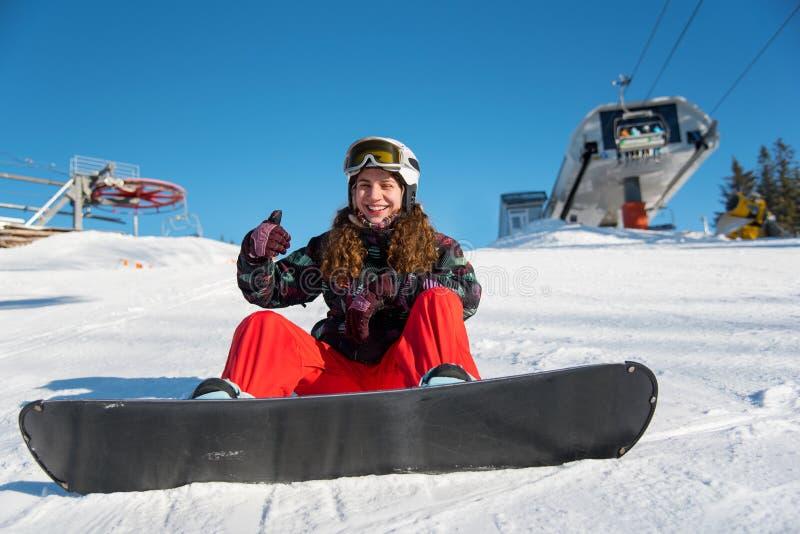 A menina do Snowboarder que senta-se na neve que mostra os polegares levanta a classe dos gestos foto de stock