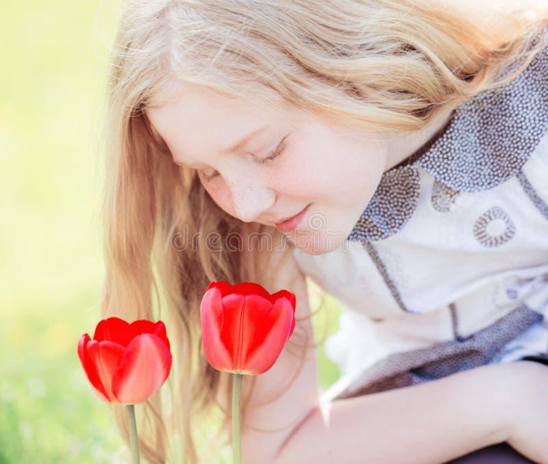 Menina do sorriso com as tulipas exteriores fotos de stock royalty free