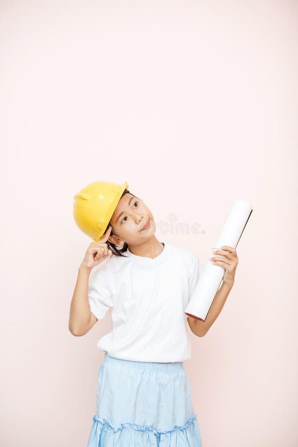 A menina do sorriso como o sonho do coordenador do arquiteto ao futuro mostra o ha imagens de stock