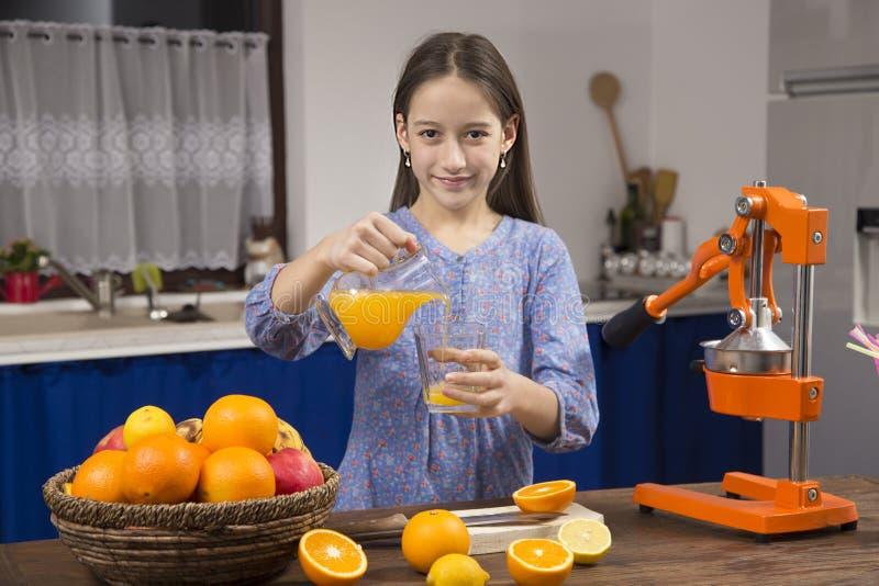 A menina do sorriso faz um suco de laranja imagem de stock royalty free