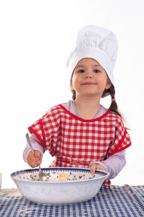 Menina do sorriso no traje do cozinheiro foto de stock