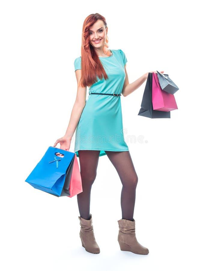 Menina do sorriso que está com sacos de compras foto de stock royalty free