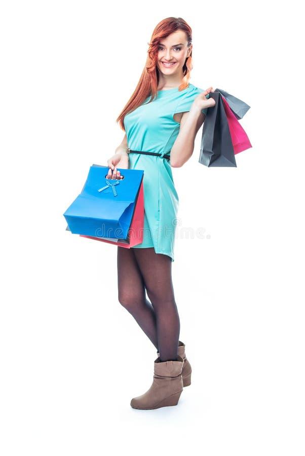 Menina do sorriso que está com sacos de compras imagem de stock royalty free