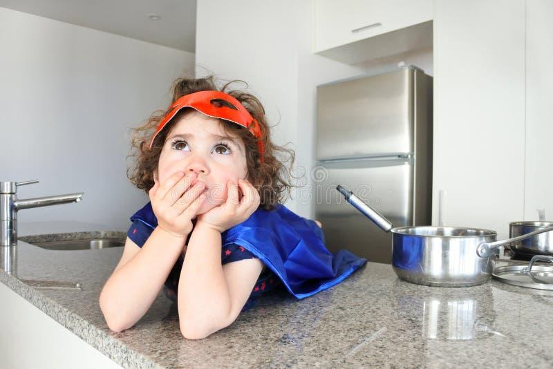 A menina do super-herói pensa sobre o que comer ou cozinhar fotos de stock