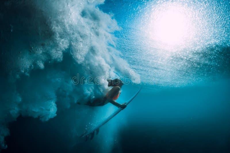 Menina do surfista com o mergulho da prancha subaquático com a onda de oceano grande inferior imagens de stock