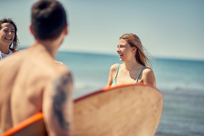 Menina do surfista Mulher 'sexy' nos povos desportivos da praia com boa da ressaca imagem de stock