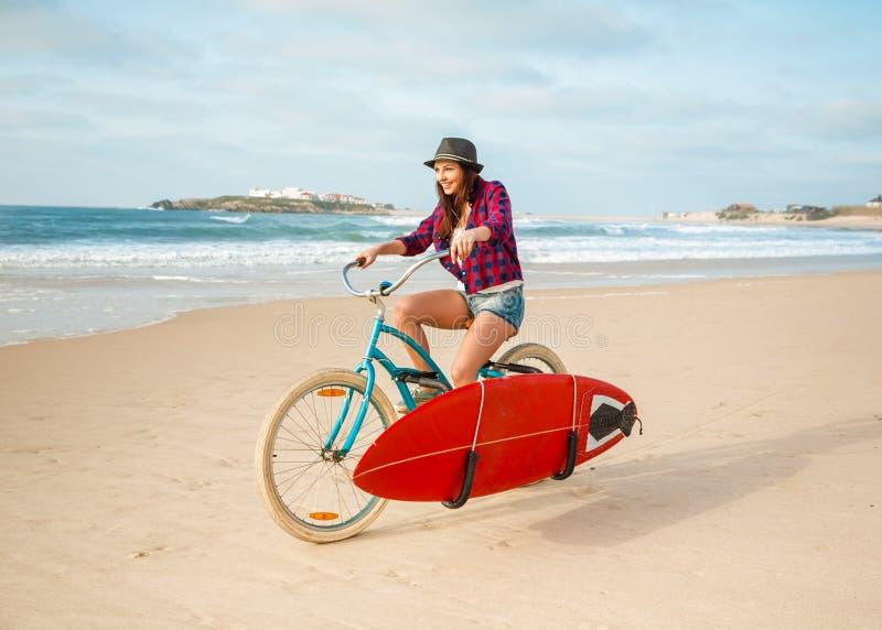 Menina do surfista que monta um bicyicle fotografia de stock