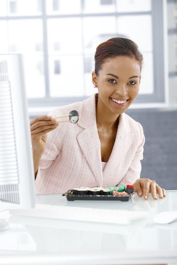 Menina do trabalhador de escritório que come o sushi imagens de stock royalty free