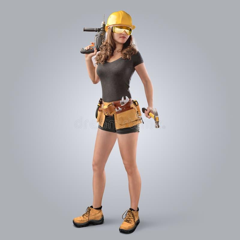 Menina do trabalhador em um capacete com broca e martelo foto de stock royalty free