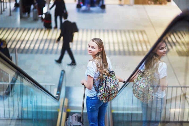 A menina do turista com trouxa e continua a bagagem no aeroporto internacional, na escada rolante fotos de stock