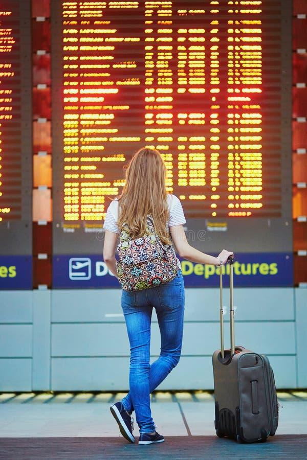 A menina do turista com trouxa e continua a bagagem no aeroporto internacional, perto da placa da informação do voo fotografia de stock