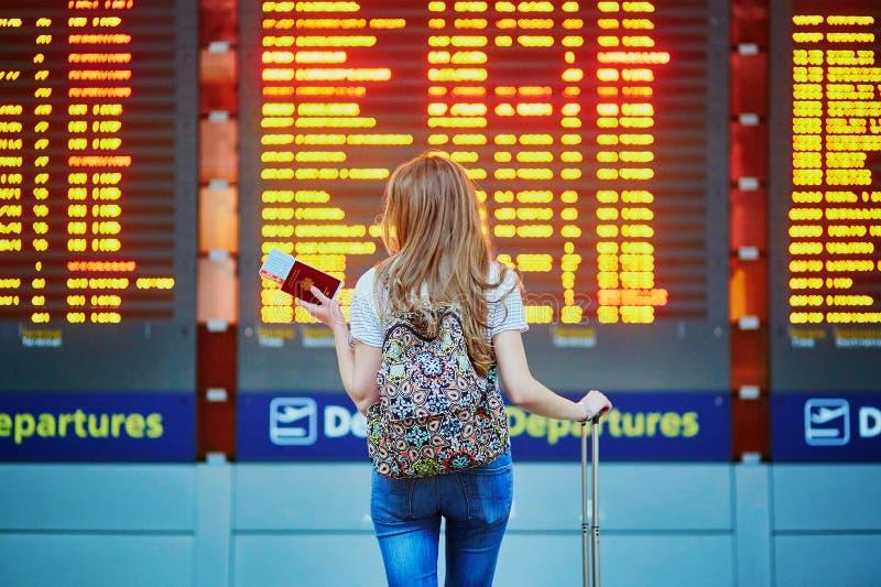 A menina do turista com trouxa e continua a bagagem no aeroporto internacional, perto da placa da informação do voo foto de stock royalty free