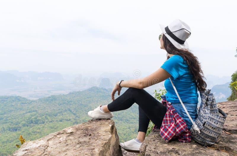 A menina do turista com a trouxa que senta-se na parte superior da montanha aprecia a paisagem bonita imagem de stock