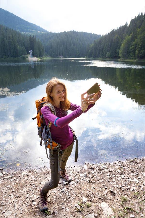 Menina do turista em um lago da montanha fotografia de stock