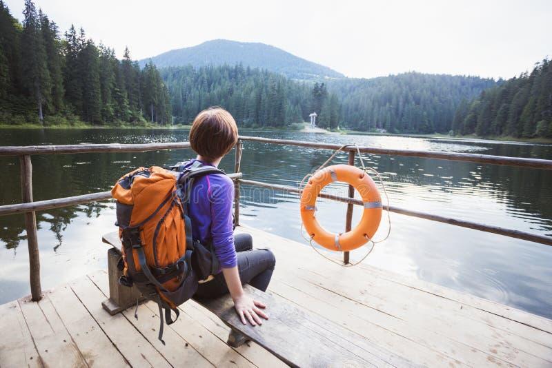 Menina do turista em um lago da montanha fotos de stock royalty free
