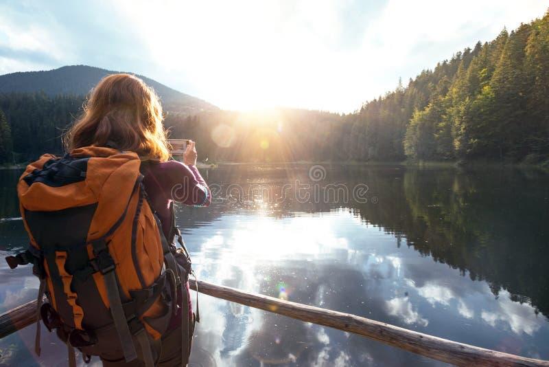 Menina do turista em um lago da montanha fotografia de stock royalty free