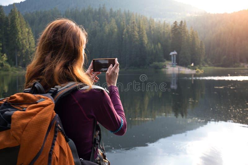 Menina do turista em um lago da montanha imagens de stock royalty free