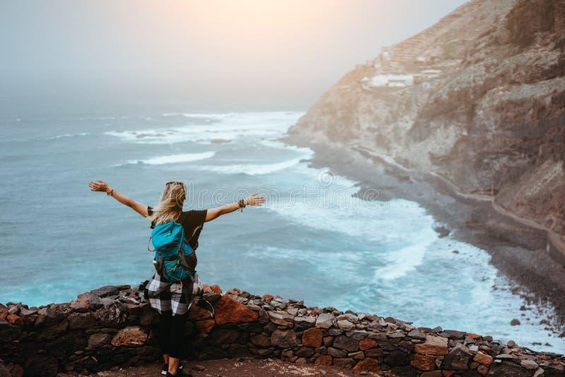 A menina do turista está feliz estar na extremidade da rota por muito tempo trekking que conduz ao longo do litoral do penhasco c imagens de stock royalty free