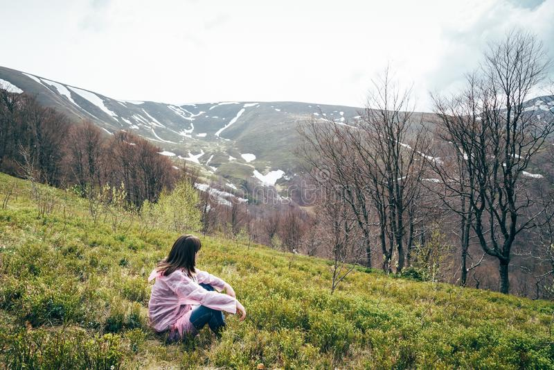 Menina do turista no revestimento cor-de-rosa da chuva que senta-se na grama que olha as montanhas cercadas pela floresta, apreci foto de stock royalty free