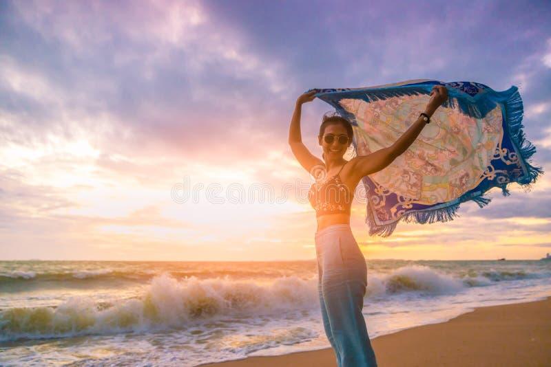 Menina do turista que relaxa com o pano de sopro no por do sol na praia fotos de stock