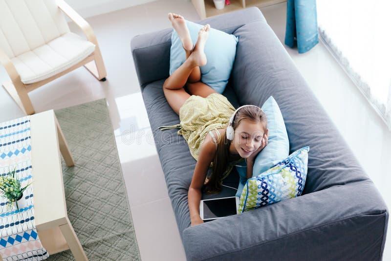 Menina do Tween que relaxa no sofá em casa imagem de stock