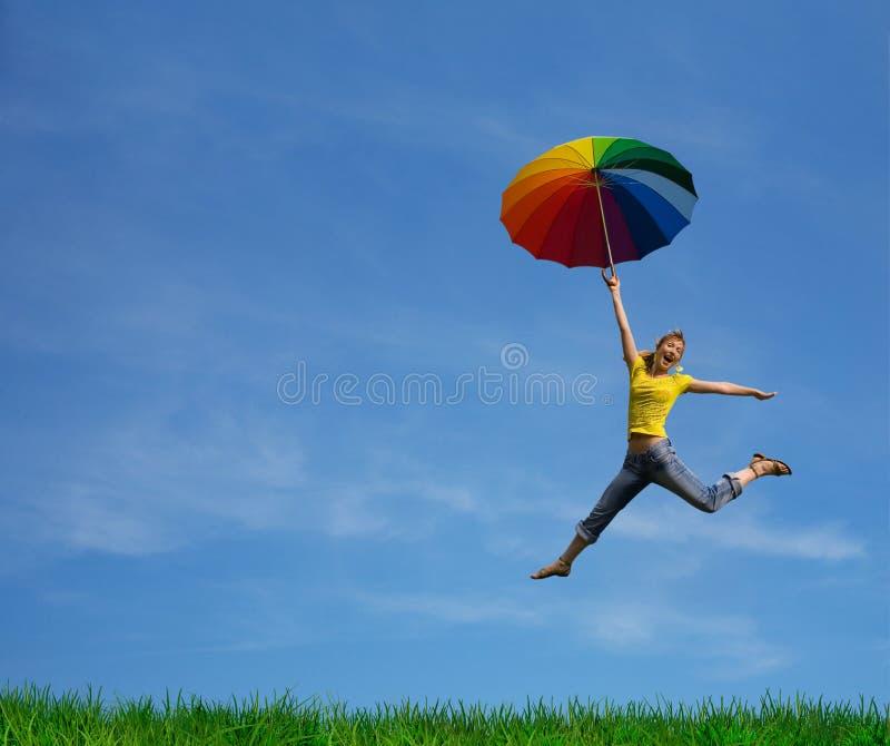 Menina do vôo com o guarda-chuva colorido no azul azul fotos de stock royalty free
