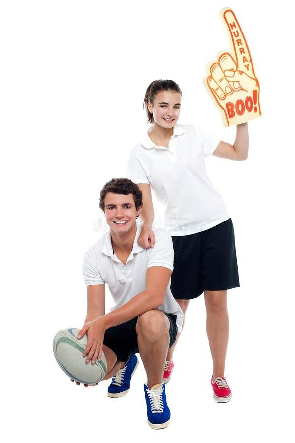 Menina do ventilador do líder da claque que levanta com jogador de futebol fotografia de stock