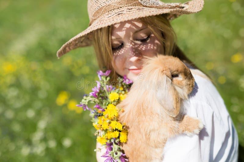 Menina do verão com o coelho na natureza imagem de stock