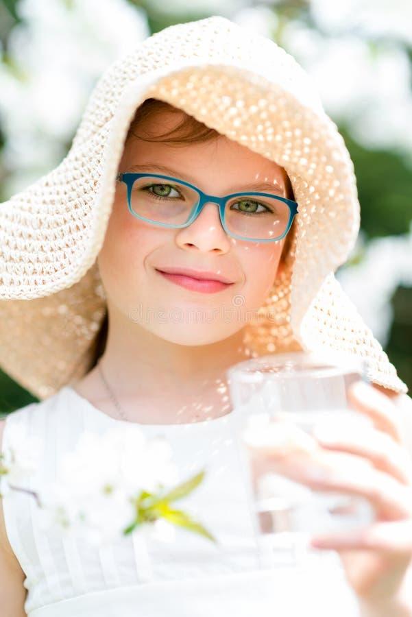 Menina do verão no retrato exterior da água potável do chapéu de palha imagem de stock royalty free