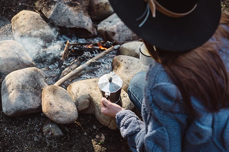 A menina do viajante no chap?u guarda o caf? quente em uma floresta pr?ximo ? fogueira fotos de stock royalty free