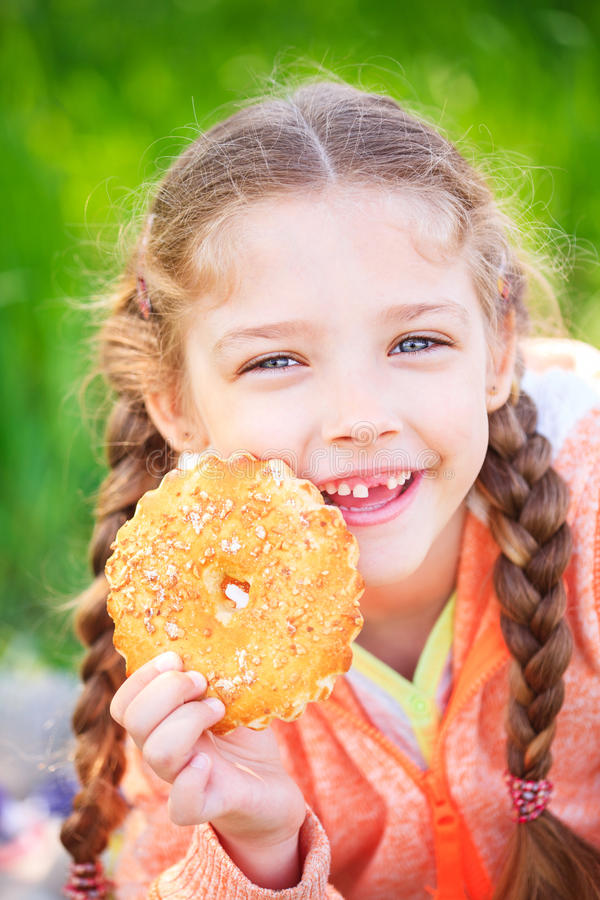 Menina doce com um dente caído que guarda cookies em sua mão fotografia de stock royalty free