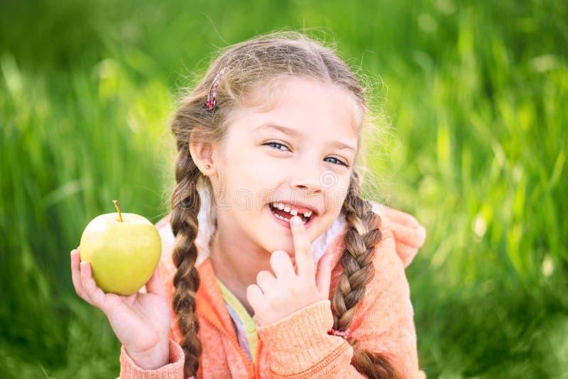 Menina doce com um toth caído que guarda uma maçã em sua mão fotografia de stock