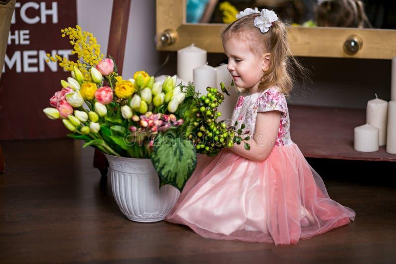 Menina doce de olhos azuis em um vestido cor-de-rosa que senta-se perto de um vaso com tulipas, mimosa, bagas e verdes e sorriso imagem de stock royalty free