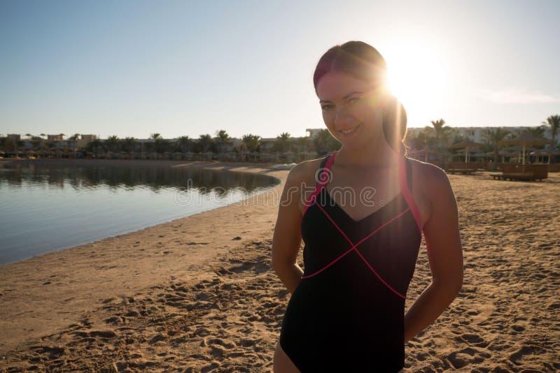 A menina doce, delgada está na praia contra o por do sol Os raios do sol brilham na câmera fotografia de stock royalty free