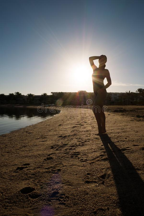 A menina doce, delgada está na praia contra o por do sol Silhueta de um nadador em um roupa de banho imagens de stock