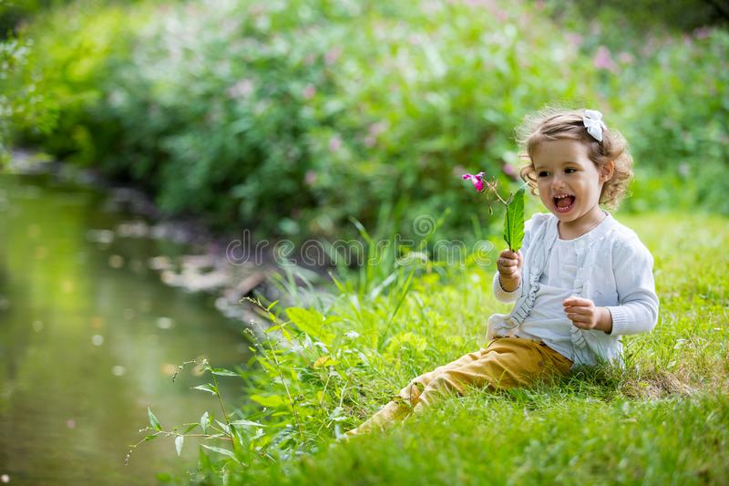 Menina doce, feliz que senta-se na grama fotos de stock royalty free