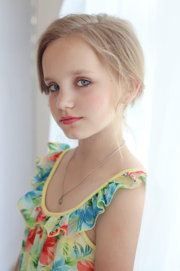 A menina doce pequena bonita com um penteado festivo com bordos e os olhos pintados está perto da janela foto de stock