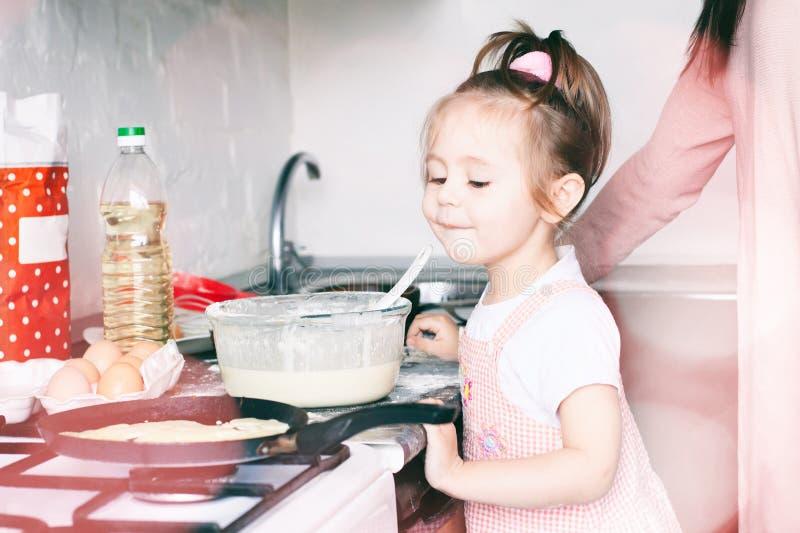 Menina doce pequena e suas panquecas da fritada da m?e no carnaval tradicional Maslenitsa Shrovetide do feriado do russo imagem de stock