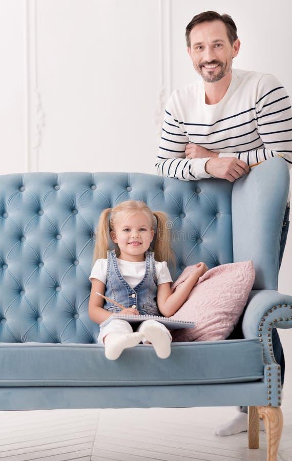 Menina doce positiva que senta-se perto do coxim imagens de stock
